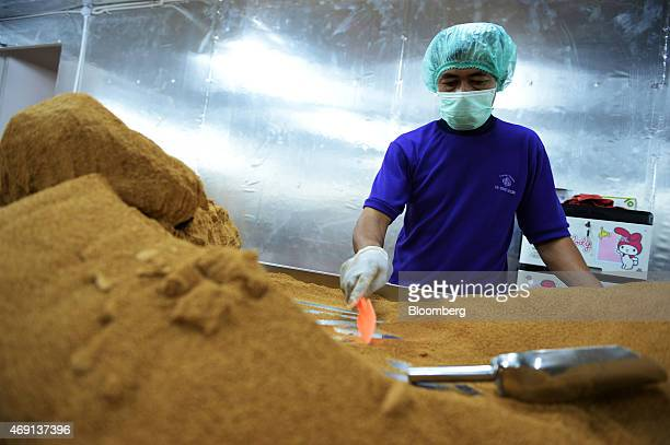 A worker uses a spatula to handle coconut palm sugar at the PT Bio Takara factory in Purwokerto Central Java Indonesia on Wednesday March 11 2015...