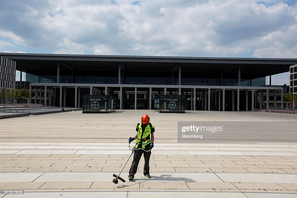 A worker uses a strimmer to remove weeds from paving in front of Berlin Brandenburg International Willy Brandt Airport in Schoenefeld, Germany, on Monday, May 3, 2016. The massively overbudget airport was planned to open in 2010 and handle 27 million passengers a year, crowning Berlin as the continent's 21st century crossroads. Photographer: Krisztian Bocsi/Bloomberg via Getty Images