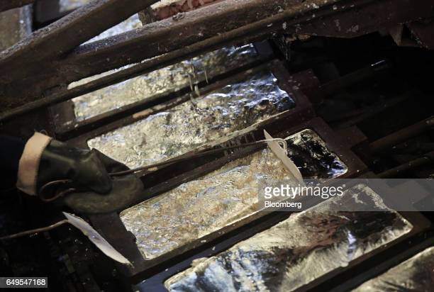 A worker uses a tool to scrape the surface of a cooling zinc ingot in the rotary foundry room at the Chelyabinsk Zinc Plant operated by Ural Mining...