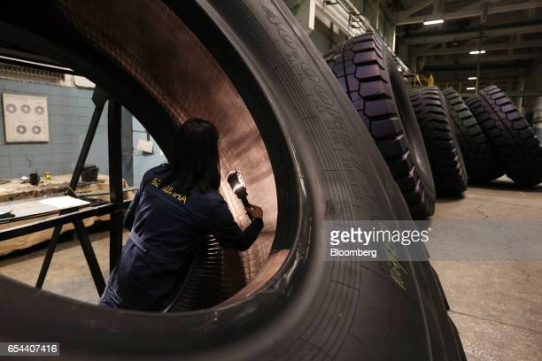 A worker uses a torch light to inspect the inside of a large 4000R57 sized tire in the control room at the Belshina JSC tire factory in Babruysk...