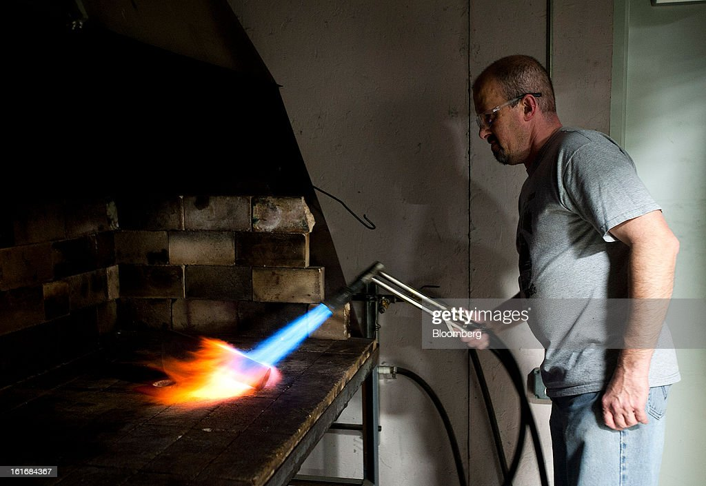 A worker uses a torch to make a piece of brass more malleable for shaping it into a trumpet bell in the manufacturing department of the E.K Blessing Co. in Elkhart, Indiana, U.S., on Thursday, Feb. 7, 2013. Photographer: Ty Wright/Bloomberg via Getty Images