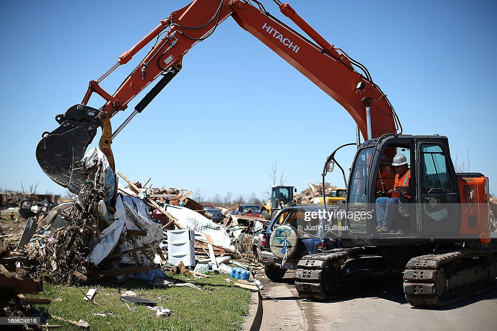 A worker uses a tractor to clean up debris from a neighborhood damaged by a tornado on June 2, 2013 in Moore, Oklahoma. Residents of Moore, Oklahoma continue to recover and sift through the remains of their homes two weeks after a devastating EF-5 tornado ripped through the town killing 24 people and destroying hundreds of homes and businesses.