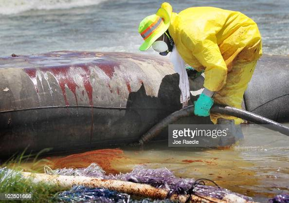 A worker uses a vacuum hose to capture some of the oil washing on to Fourchon Beach from the Deepwater Horizon oil spill in the Gulf of Mexico on...
