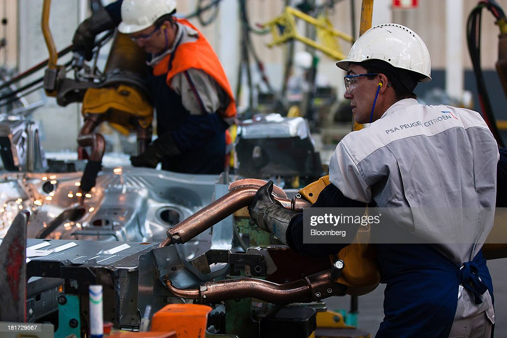 A worker uses a welding machine to weld the body panel of a Citroen Berlingo automobile at the PSA Peugeot Citroen production plant in Mangualde, Portugal, on Monday, Sept. 23, 2013. Some economists point to falling labor costs across southern Europe as a sign the region may be becoming more attractive as a manufacturing base. Photographer: Mario Proenca/Bloomberg via Getty Images