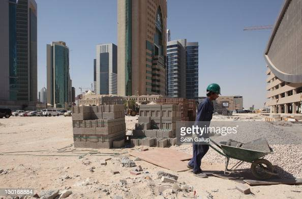 A worker uses a wheelbarrow to move cinder blocks on a construction site in the budding new financial district on October 23 2011 in Doha Qatar Qatar...