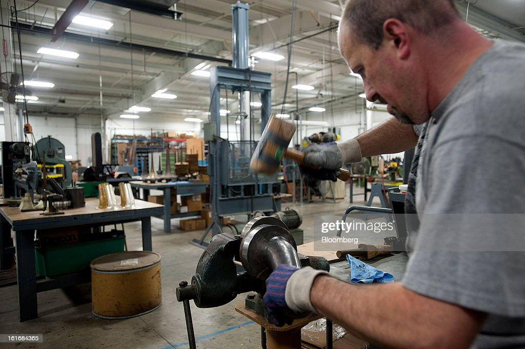 A worker uses a wooden hammer to shape a piece of brass on a metal mold into a trumpet bell in the manufacturing department of the E.K Blessing Co. in Elkhart, Indiana, U.S., on Thursday, Feb. 7, 2013. Photographer: Ty Wright/Bloomberg via Getty Images