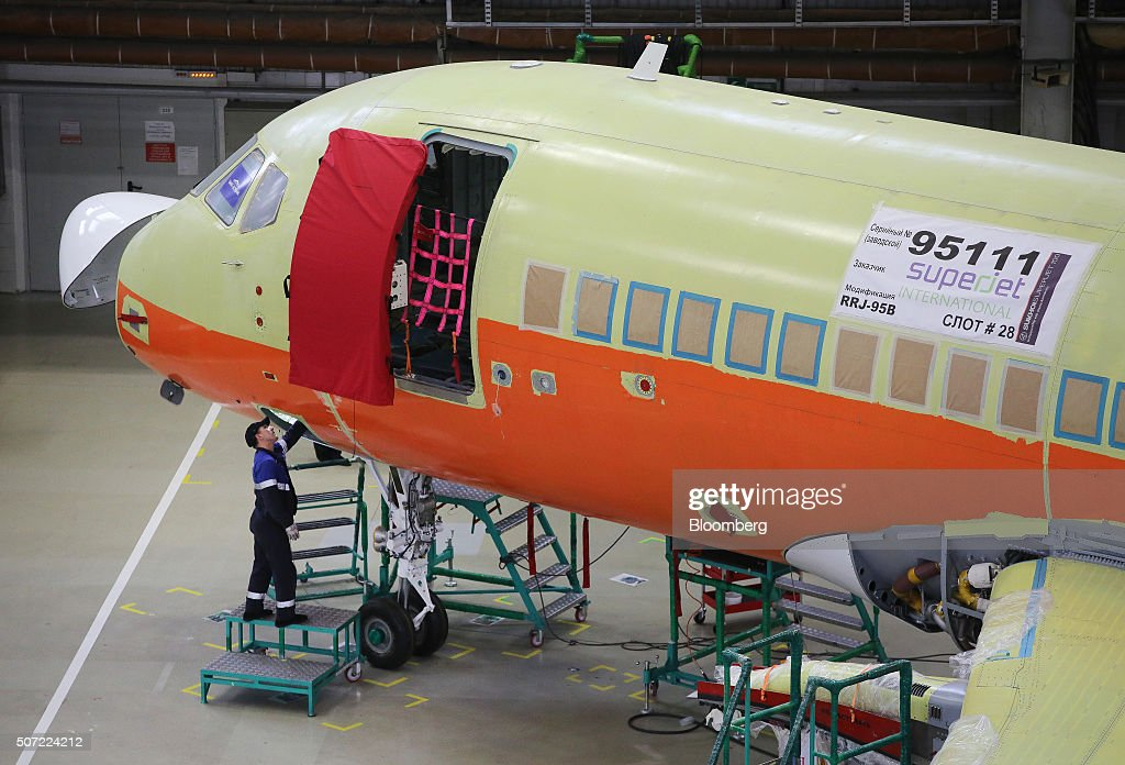 A worker uses an access panel beneath the cockpit to fit systems to a Sukhoi Superjet 100 aircraft during construction at the Sukhoi Civil Aircraft...