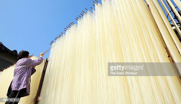 A worker uses chopsticks to stretch drying somen noodles on February 11 2015 in Yokkaichi Mie Japan Somen is a type of Japanse wheat noodle served...