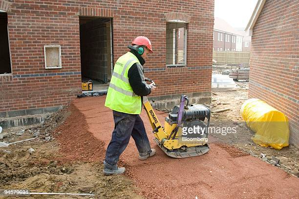 A worker uses machinery to lay the foundations for a path at a Bryant Homes development a subsidiary of Taylor Woodrow at Hermitage Berkshire England...