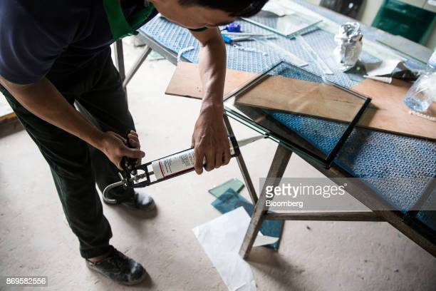 A worker uses silicon while making a double pane glass panel at the Somvang Glass Factory on the outskirts of Vientiane Laos on Wednesday Nov 1 2017...