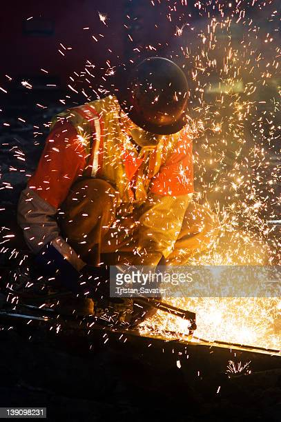 Worker using an oxy-acetylene cutting torch