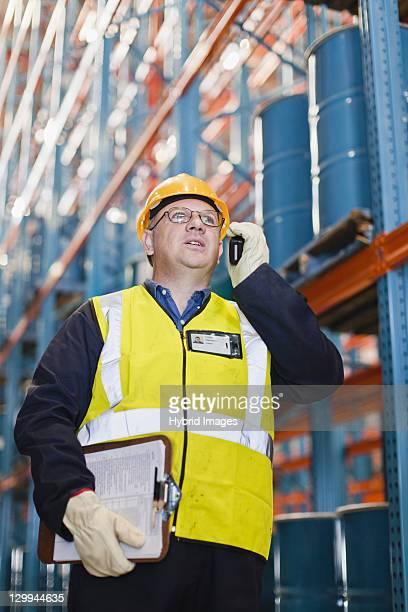 Travailleur à l'aide de téléphone portable dans le warehouse