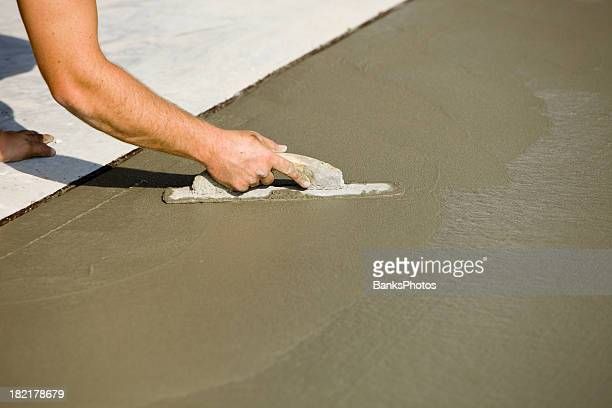Worker Using Concrete Trowel to Smooth Driveway