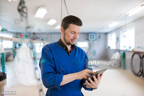 Worker using digital tablet at fishing industry