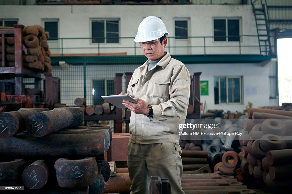 Worker using digital tablet in hydraulics factory : Stock Photo