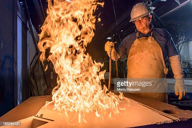 Worker using flames to cure a mould in foundry