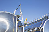 Worker using laptop on platform above stainless steel milk tanker