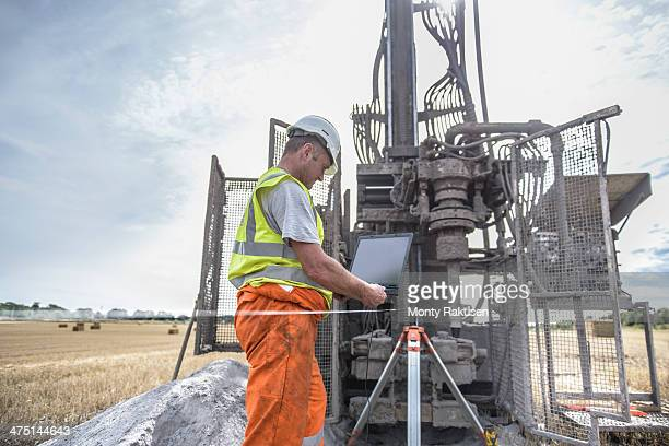 Worker using laptop to survey drilled hole made by drilling rig in field
