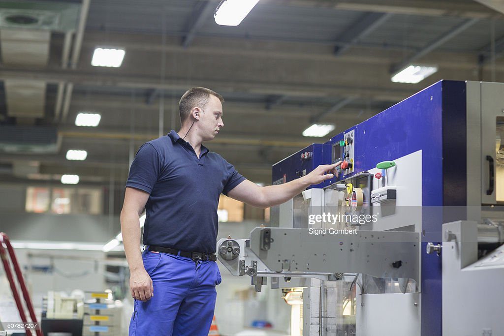 Worker using machine in paper packaging factory