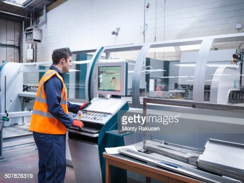 Worker using robotic metal cutting machine in sheet metal factory