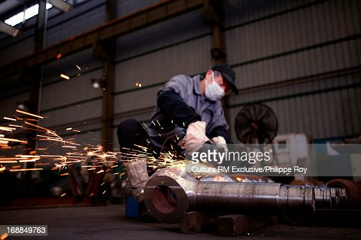Worker using saw on metal in hydraulics factory : Stock Photo