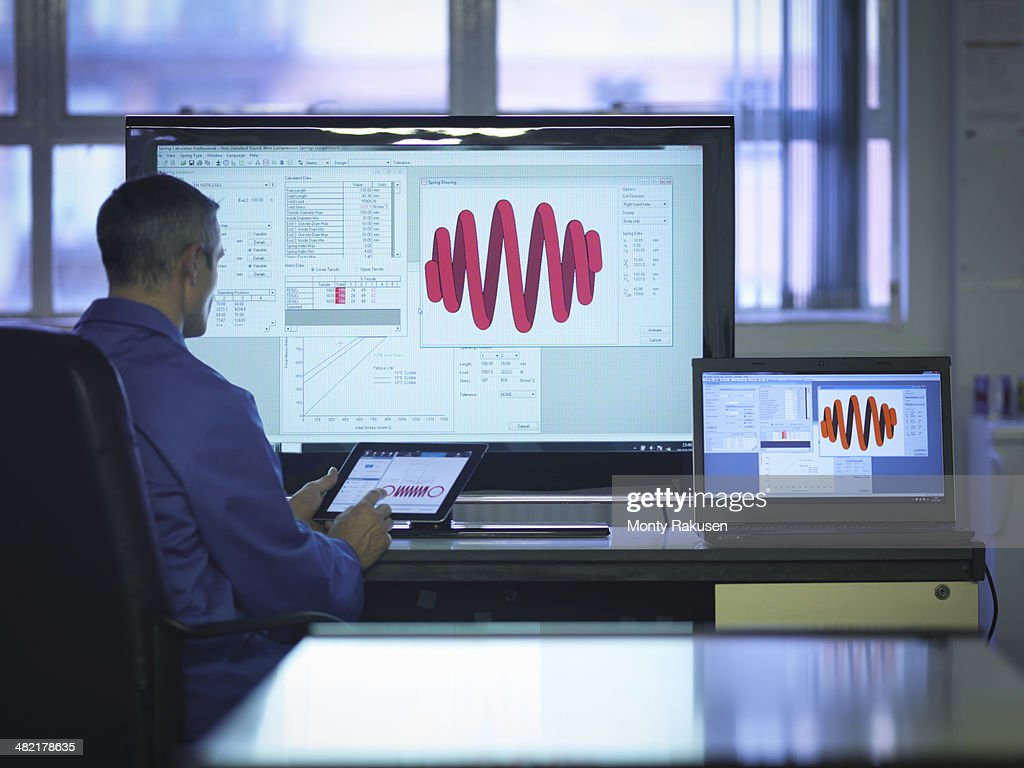 Worker using software to calibrate springs in office