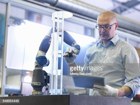 Worker using tablet to perform quality control checks in glass factory