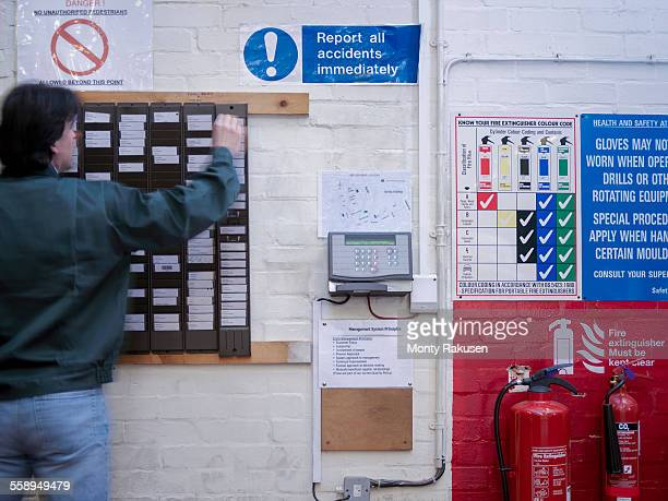 Worker using time clock in factory