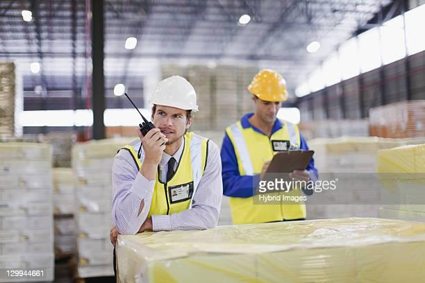 Worker using walkie talkie in warehouse