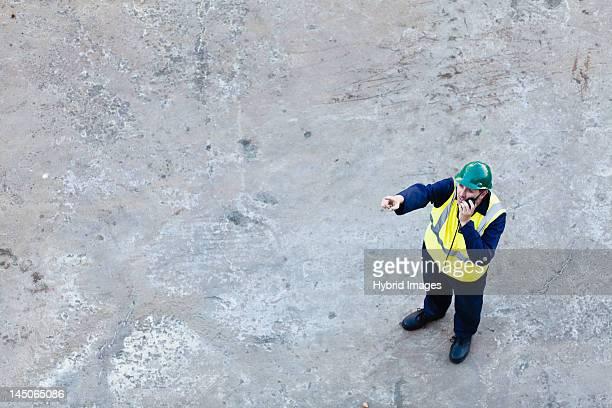 Worker using walkie-talkie on dry dock