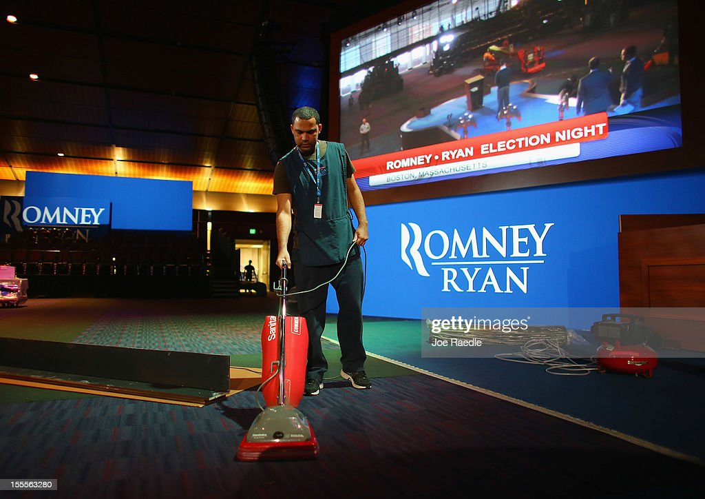 A worker vacuums the carpet as the stage is set up at the Boston Convention and Exhibition Center for Mitt Romney Campaign's election night event November 5, 2012 in Boston, Massachusetts. National polls show that Romney and U.S. President Barack Obama are in a virtual dead heat in the race for the presidential election on Tuesday.