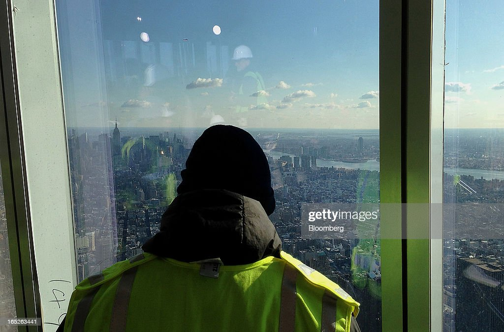 A worker views the Manhattan skyline from the One World Trade Center observation deck during a media tour in New York, U.S., on Tuesday, April 2, 2013. The observation deck at One World Trade Center, expected to open in 2015, will occupy the tower's 100th through 102nd floors. Guests visiting the observation deck will see a 'pre-show' about the creation of the building while waiting in line in the lobby. Photographer: Victor J. Blue/Bloomberg via Getty Images