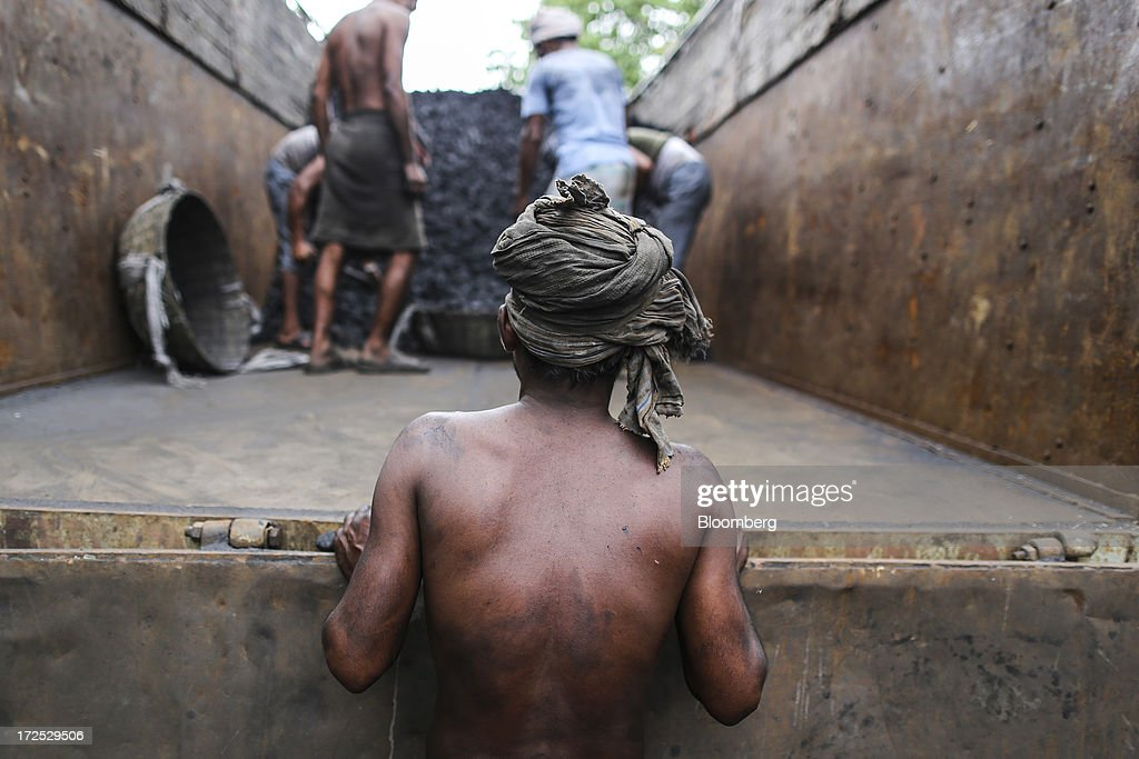 A worker waits as fellow workers fill a basket with coal during the unloading of a truck at a coal wholesale market in Mumbai, India, on Tuesday, July 2, 2013. India, the worlds third-largest coal consumer, imported 43 percent more of the fuel than a year ago on increased demand from power stations and steelmakers, according to shipping data, and is set to eclipse China as the top importer of power station coal by 2014. Photographer: Dhiraj Singh/Bloomberg via Getty Images
