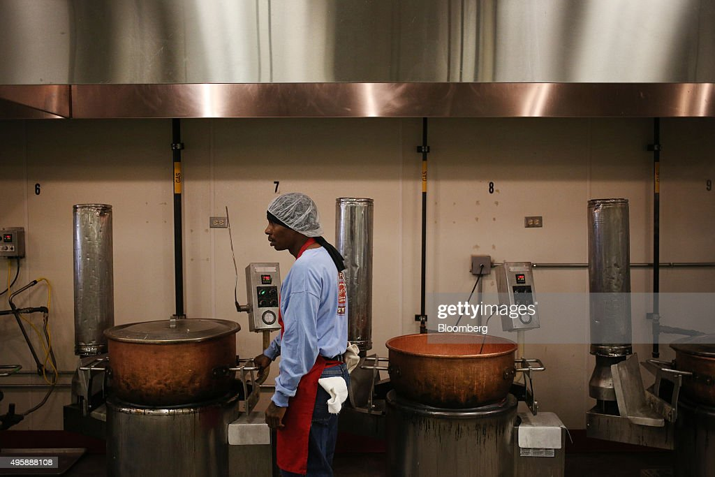 A worker waits for a kettle of corn syrup candy to cook before it is cooled and stretched into candy canes at the Hammond's Candies production...