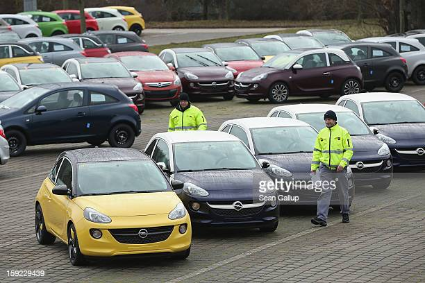 Worker walk past finished Opel Adam cars at a factory parking lot shortly after a celebration to mark the launch of the new Opel compact car at the...