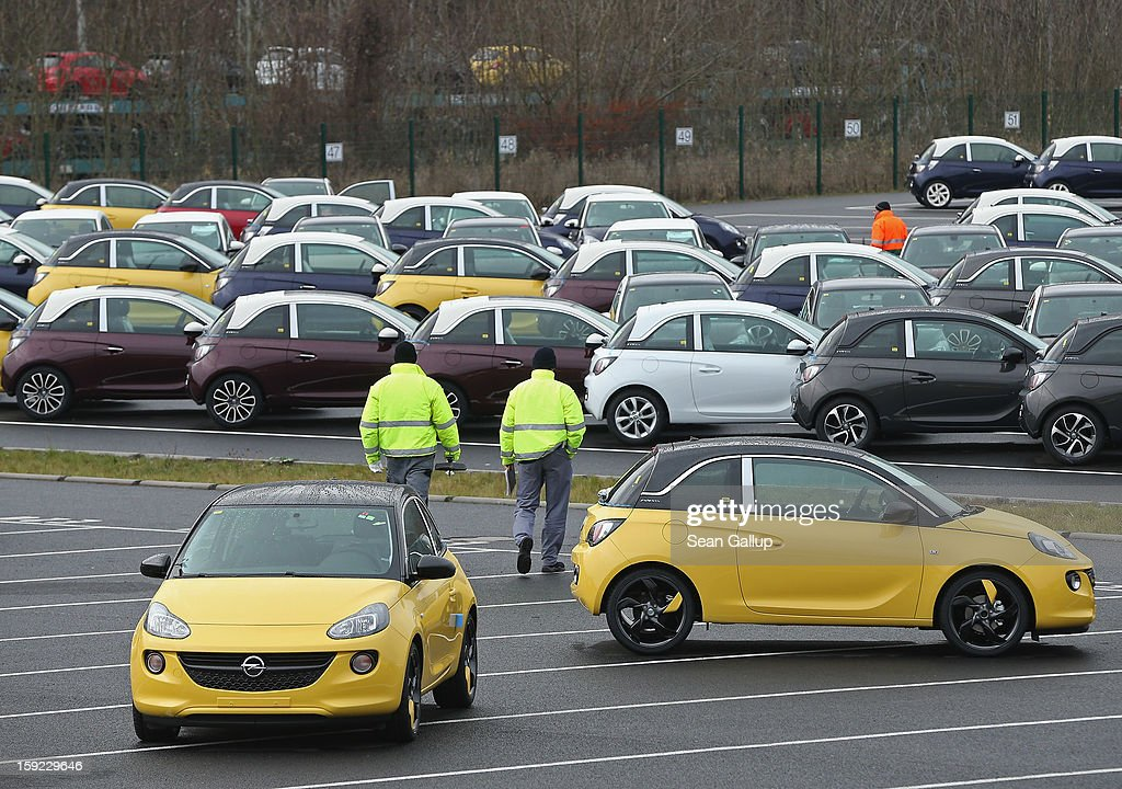Worker walk past finished Opel Adam cars at a factory parking lot shortly after a celebration to mark the launch of the new Opel compact car at the Opel factory on January 10, 2013 in Eisenach, Germany. Opel employees hope the car will help the compny return to profits after years of sagging sales and the announcement of the Bochum factory closure in 2016.