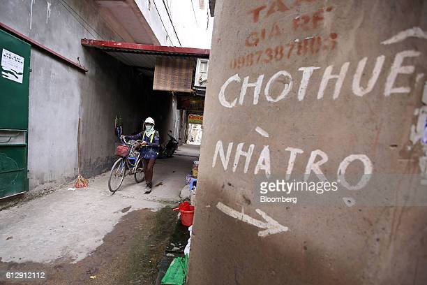 A worker walks a bicycle through an alleyway as signage on a wall reads 'Room for rent' in Ap Don hamlet Bac Ninh Province Vietnam on Thursday Sept 1...