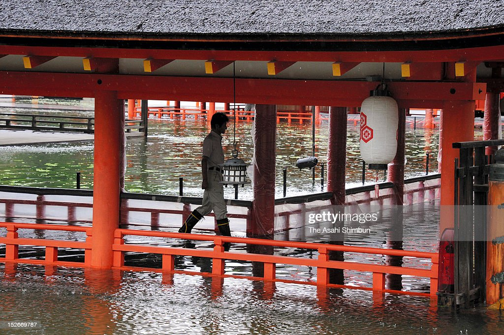 A worker walks a flooded corridor of the Itsukushima Shrine due to the heavy rain triggered by the approach of the Typhoon Sanba on September 17, 2012 in Hatsukaichi, Hiroshima, Japan.