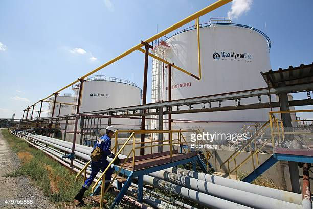 A worker walks across pipelines near oil and gas storage tanks at the Atyrau oil refinery operated by KazMunaiGas National Co in Atyrau Kazakhstan on...