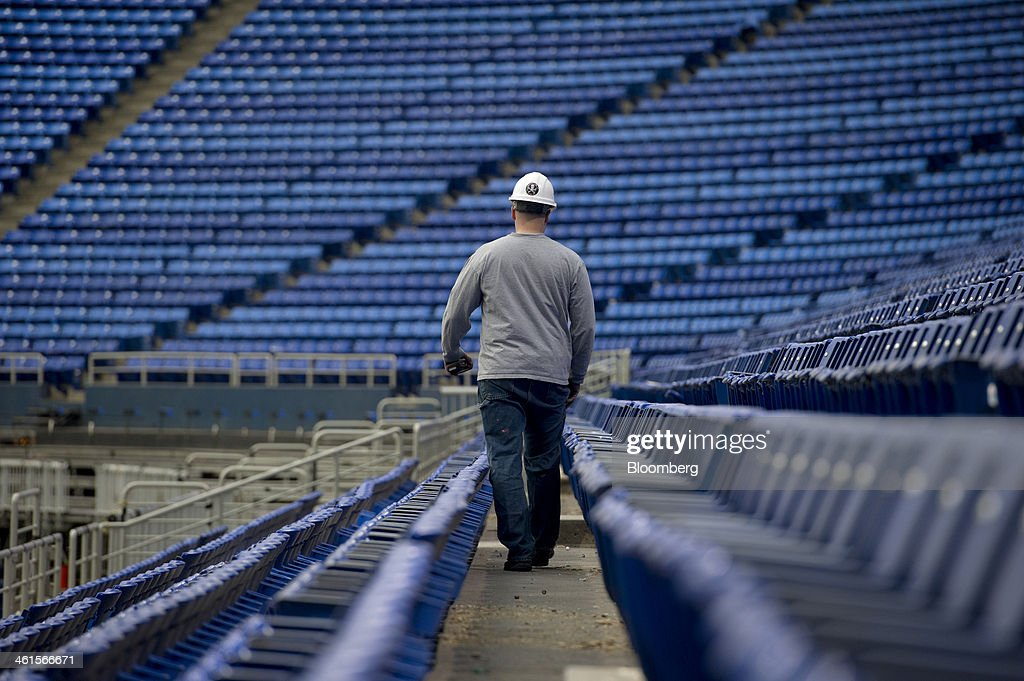 A worker walks along a row of stadium seating during the early stages of demolition of the Hubert H. Humphrey Metrodome in Minneapolis, Minnesota, U.S., on Tuesday, Jan. 7, 2014. The new stadium is expected to generate development in downtown Minneapolis and provide a venue for national events such as the Super Bowl, said Michele Kelm-Helgen, chair of the Minnesota Sports Facilities Authority, which is overseeing the project at the site of the existing Metrodome. Photographer: Matthew Hintz/Bloomberg via Getty Images