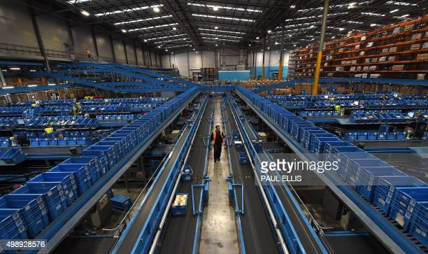 A worker walks alongside a conveyor belt as items are sorted into crates to be sent to retail stores from the Argos Distribution Centre in...