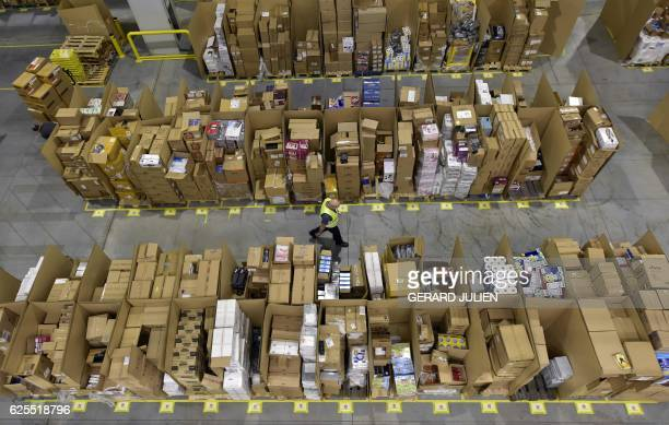 A worker walks among packages stored at the Amazon electronic commerce company's logistics center in San Fernando de Henares near Madrid on the eve...