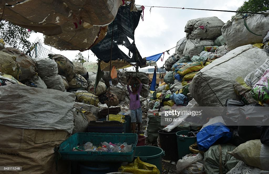 A worker walks amongst bales of collected recyclable materials at a junk shop near the former dumpsite and landfill named 'Smokey Mountain' in Manila on June 26, 2016. Incoming Philippine president Rodrigo Duterte pledged on May 26 to spread economic activity beyond the overpopulated capital of Manila, calling it a 'dead' city overrun by shantytowns. / AFP / TED