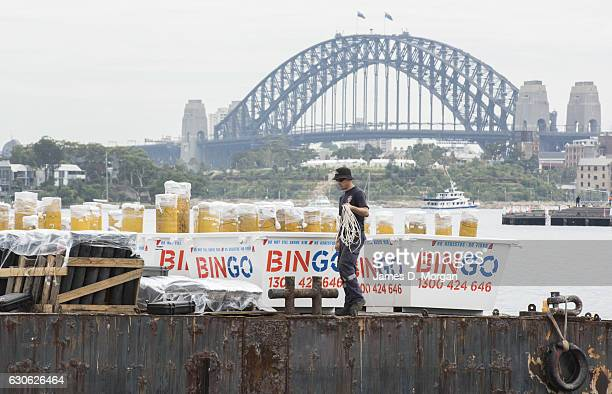 A worker walks around fireworks under protective film as they sit on barges on December 29 2016 in Sydney Australia Sydney's New Year's Eve fireworks...