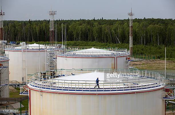 A worker walks around the perimeter of an oil storage tank at an oil plant operated by Salym Petroleum in Salym KhantyMansi autonomous region Russia...