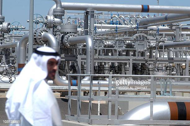 A worker walks at the Gathering Center 15 oil facility 28 March 2005 in the northern AlRawdhatain oilfield 80 Kms from Kuwait City OPECmember Kuwait...