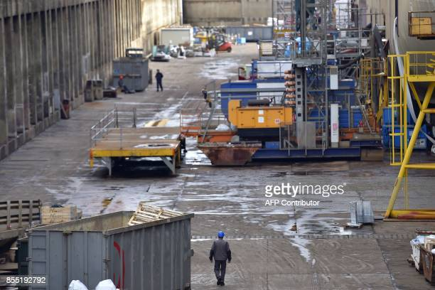A worker walks at the site of French shipyard STX in SaintNazaire western France on September 28 2017 Italian shipbuilder Fincantieri will take...
