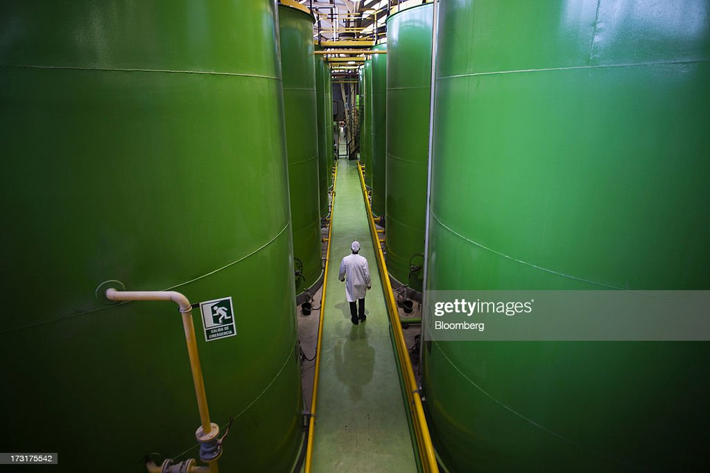 A worker walks between storage vats of Spanish olive oil at the Carbonell SA plant, operated by Deoleo SA, in Alcolea, Spain, on Tuesday, July 9, 2013. JPMorgan was asked to explore sale of more than 30% stake in olive oil company Deoleo, Reuters reports, citing two people close to the deal. Photographer: Angel Navarrete/Bloomberg via Getty Images
