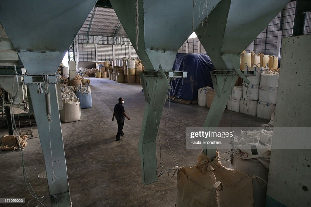 A worker walks by bags of rice at the Settapanich -Samchuk rice mill in on June 20, 2013 in Suphan Buri, Thailand. Thailand plans to sell as much as 7 million metric tons from inventories in order to fund a grain purchase program. Recently financial sources revealed that the actual losses from the government's controversial rice pledging scheme for the 2011-12 rice harvest year are close to reaching 200 billion baht [US$6.5 billion], this is far above the Thai Finance Ministry's earlier forecast of 70-100 billion baht.
