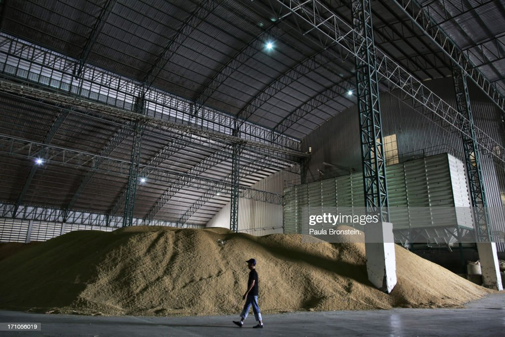 A worker walks by bags of rice at the Settapanich-Samchuk rice mill in on June 20, 2013 in Suphan Buri, Thailand. Thailand plans to sell as much as 7 million metric tons from inventories in order to fund a grain purchase program. Recently financial sources revealed that the actual losses from the government's controversial rice pledging scheme for the 2011-12 rice harvest year are close to reaching 200 billion baht [US$6.5 billion], this is far above the Thai Finance Ministry's earlier forecast of 70-100 billion baht.